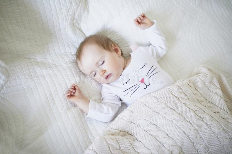 Adorable baby girl sleeping in crib under knitted blanket stock photography