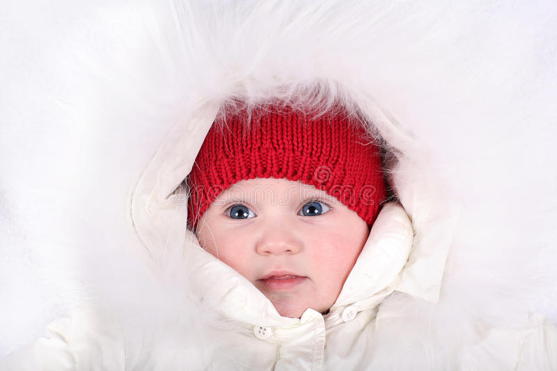 Adorable baby girl wearing red hat and white fur hood royalty free stock photo