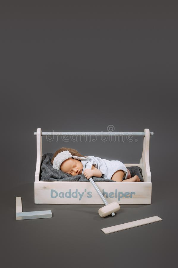 Adorable baby with hammer in hand sleeping in wooden toolbox with daddys. Helper lettering royalty free stock photography