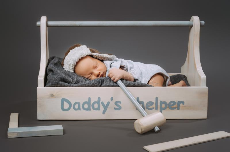 Adorable baby with hammer in hand sleeping in wooden toolbox with daddys. Helper lettering stock photo