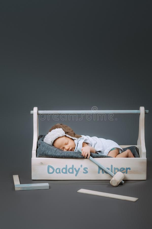 Adorable baby with hammer in hand sleeping in wooden toolbox with daddys. Helper lettering royalty free stock photo