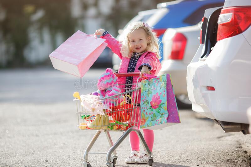 Girl three years old with a shopping trolley and paper bags in the parking lot near the supermarket. stock photo