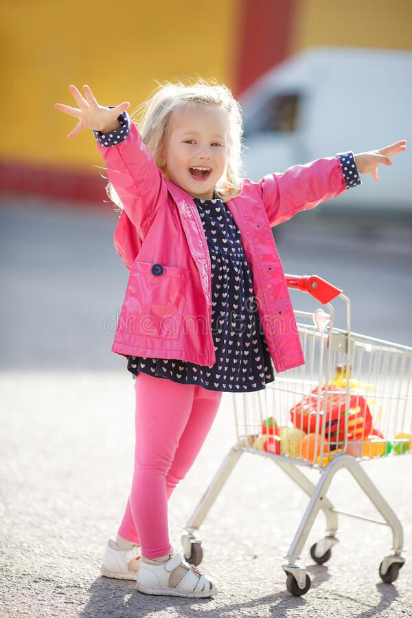 Girl three years old with a shopping trolley and paper bags in the parking lot near the supermarket. royalty free stock photos