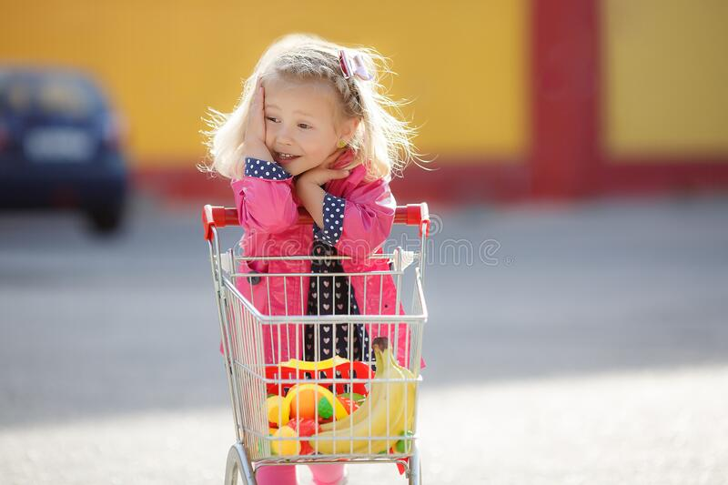 Girl three years old with a shopping trolley and paper bags in the parking lot near the supermarket. royalty free stock photo