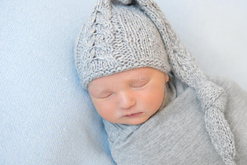 Adorable baby with knitted gray hat, napping stock image