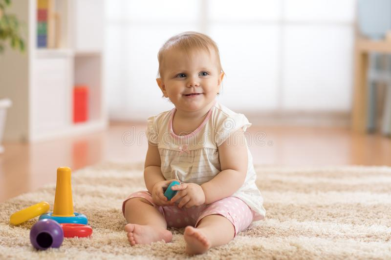 Adorable baby playing with colorful rainbow toy pyramid sitting on rug in white sunny bedroom. Toys for little kids royalty free stock photos