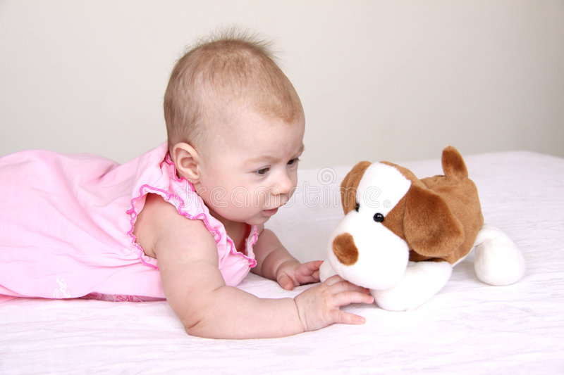 Adorable baby playing with puppy toy. 3months baby girl in pink dress playing with puppy toy stock photography
