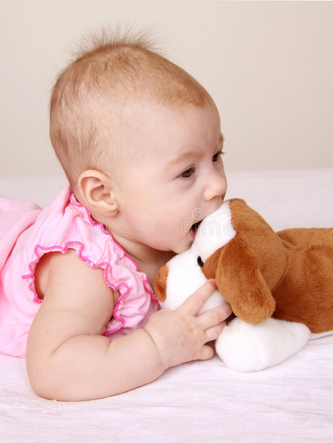 Adorable baby playing with puppy toy. 3months baby girl in pink dress playing with puppy toy royalty free stock images