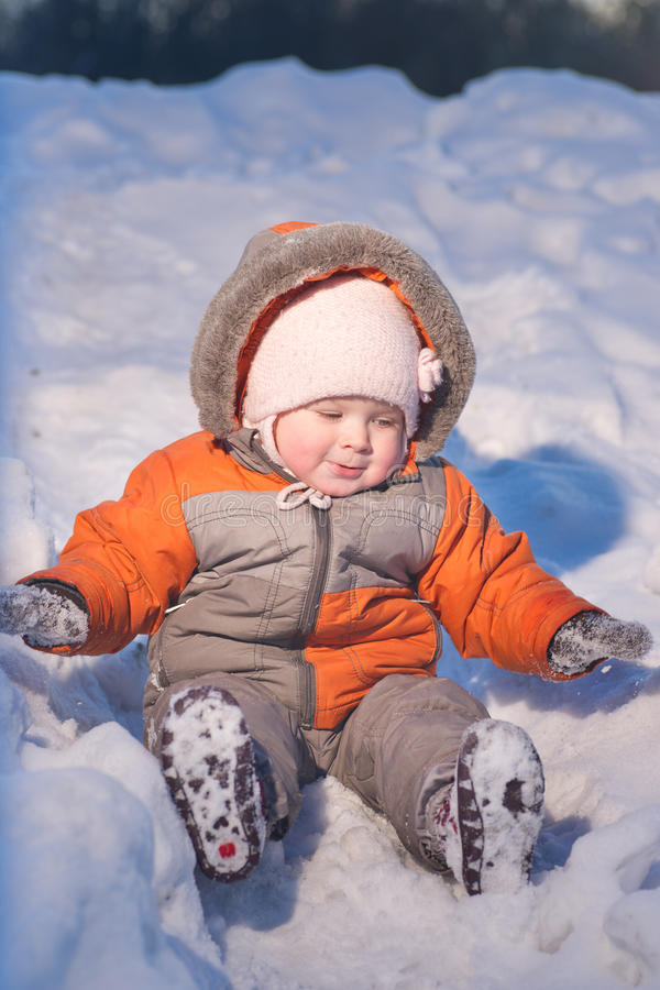 Adorable baby sliding down from snow hill stock image