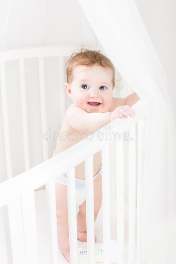 Adorable baby wearing a diaper standing in a white round crib. Adorable ;ottle baby wearing a diaper standing in a white round crib stock image