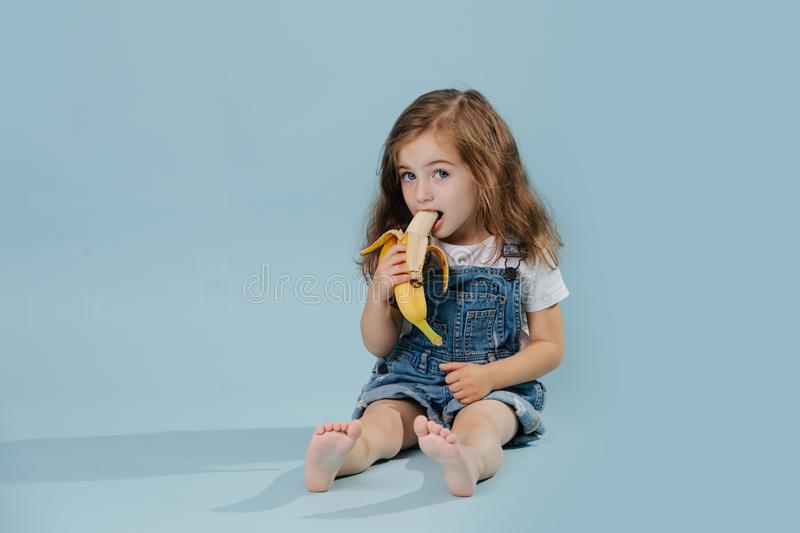 Little girl is eating banana, while sitting on the floor over blue background royalty free stock image