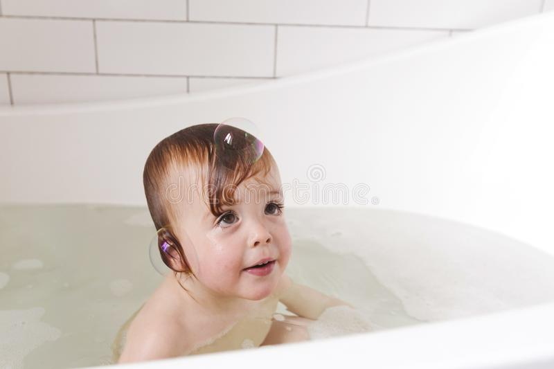 Adorable bath baby boy with soap suds on hair stock photo