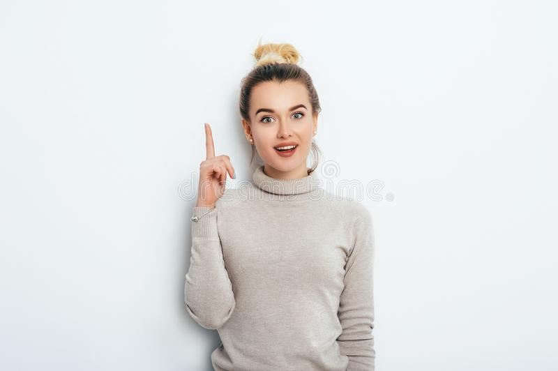 Adorable beautiful young woman with hair bun in sweater gets good idea in mind raised forefinger on isolated white background. royalty free stock image