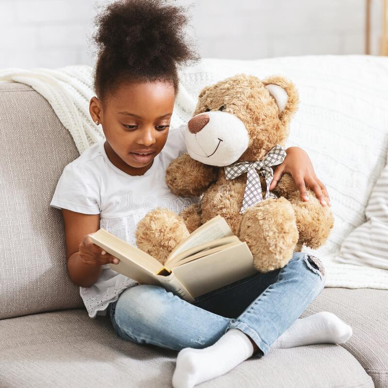 Free Adorable Black Kid With Teddy Bear Reading Book Royalty Free Stock Photography - 170116007