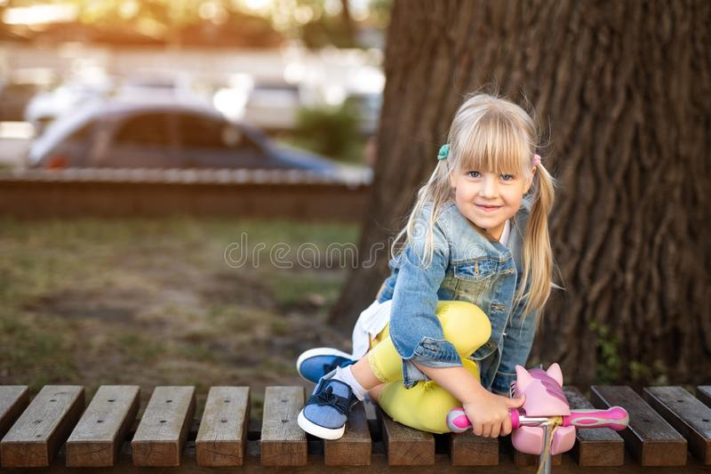 Adorable blond caucasian preschooler fashionista girl wearing jeans and bright yellow leggins sitting over wooden bench and. Smiling at city park or street at royalty free stock images