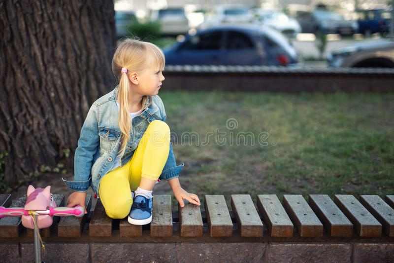 Adorable blond caucasian preschooler fashionista girl wearing jeans and bright yellow leggins sitting over wooden bench and. Smiling at city park or street at stock image