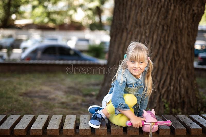 Adorable blond caucasian preschooler fashionista girl wearing jeans and bright yellow leggins sitting over wooden bench and. Smiling at city park or street at stock photos