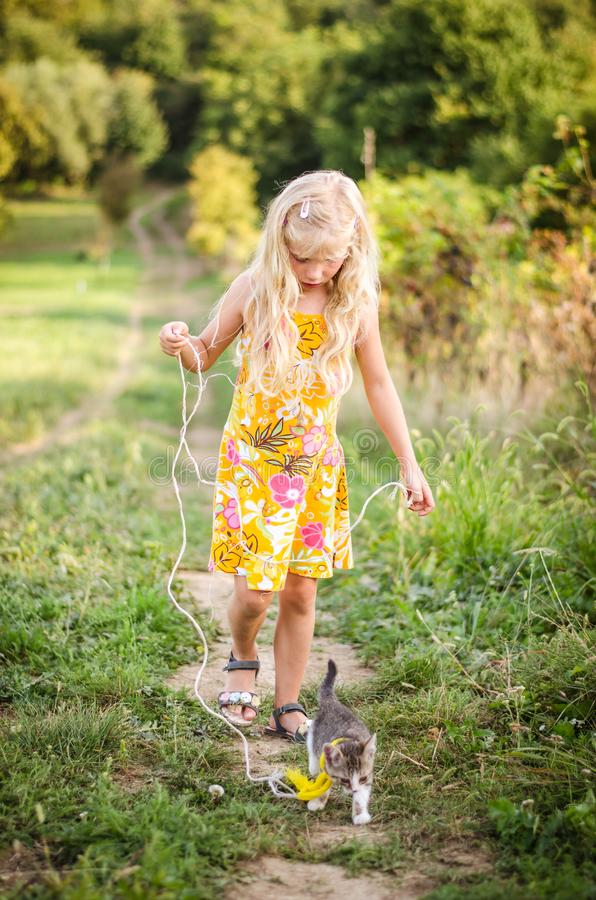 Little child walking with cat in lead royalty free stock image