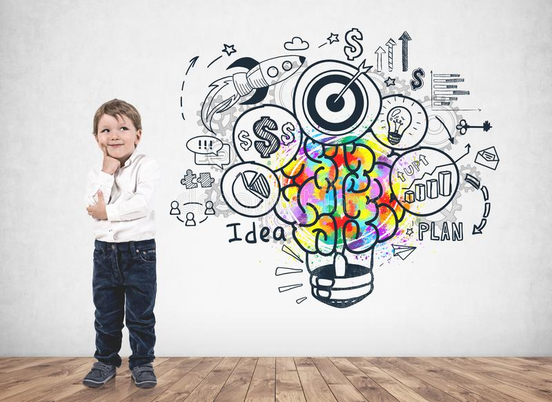 Thoughtful little boy, business idea. Adorable blond little boy wearing white shirt and thinking standing near concrete wall with colorful business idea sketch stock photography