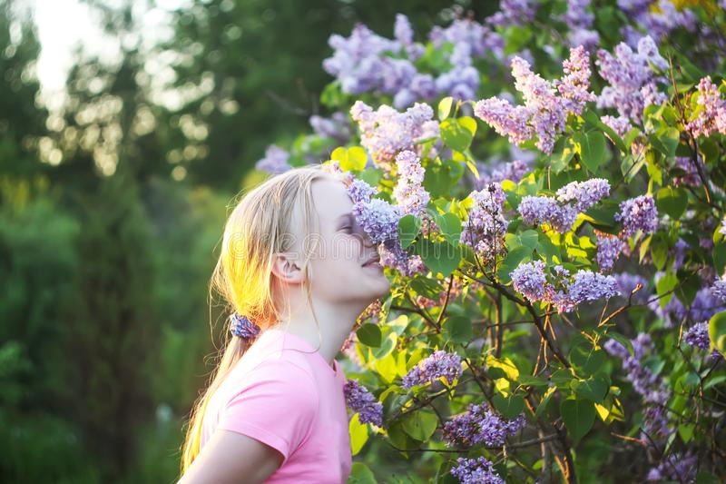 Adorable blonde girl on spring blooming bush of lillac background in a park. stock photos