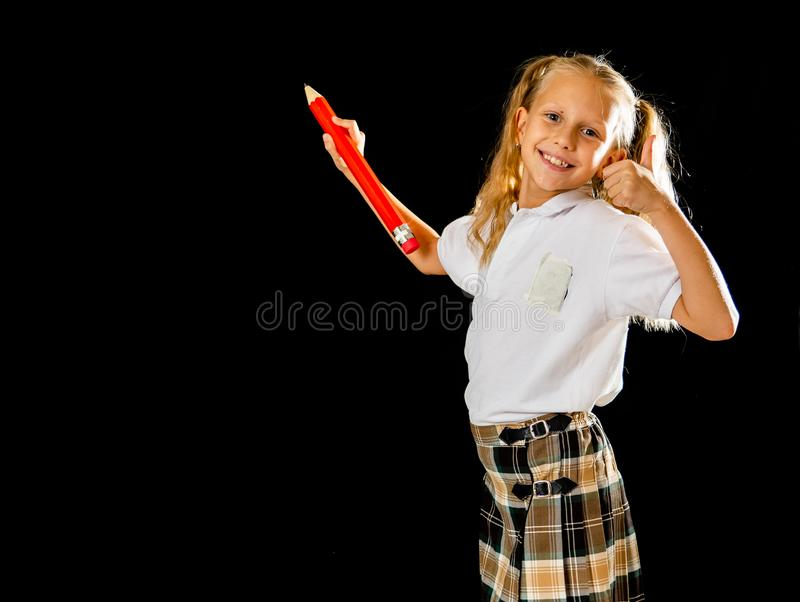 Adorable blonde haired schoolgirl with two ponytail and uniform writing on the blackboard feeling happy showing the thumb up royalty free stock image