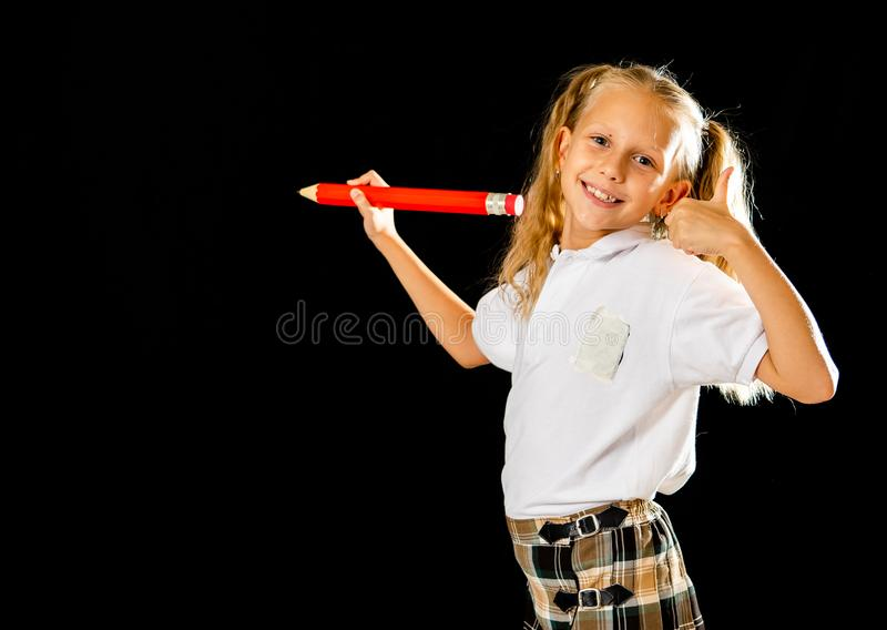 Adorable blonde haired schoolgirl with two ponytail and uniform writing on the blackboard feeling happy showing the thumb up. Gesture isolated on black stock photography