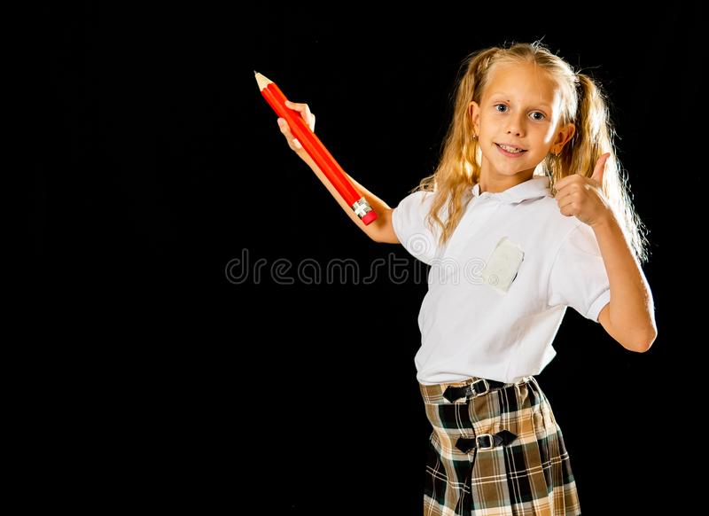 Adorable blonde haired schoolgirl with two ponytail and uniform writing on the blackboard feeling happy showing the thumb up stock images