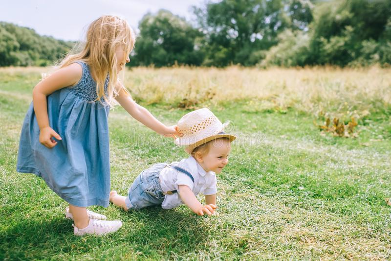 adorable blonde siblings playing in green royalty free stock photography