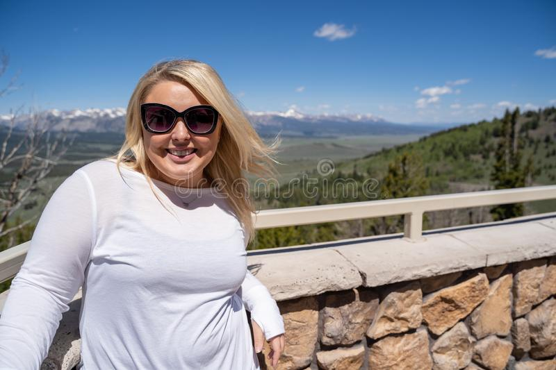 Adorable blonde woman smiles and poses for a tourist photo at the Galena Summit Overlook in the Sawtooth Mountains of Idaho royalty free stock photography