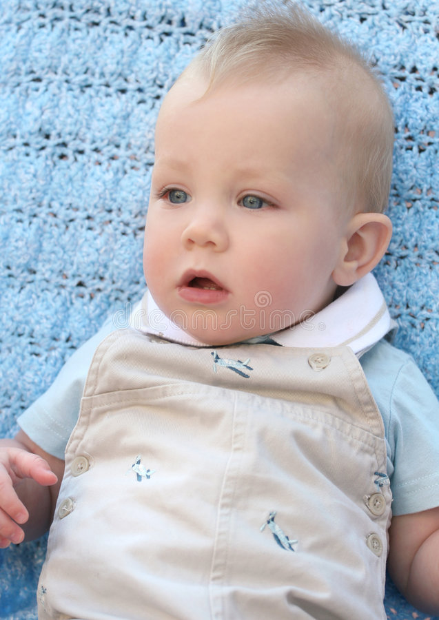 Adorable Blue Eyed Baby Boy. Adorable baby boy with blue eyes on blue blanket / background stock photography