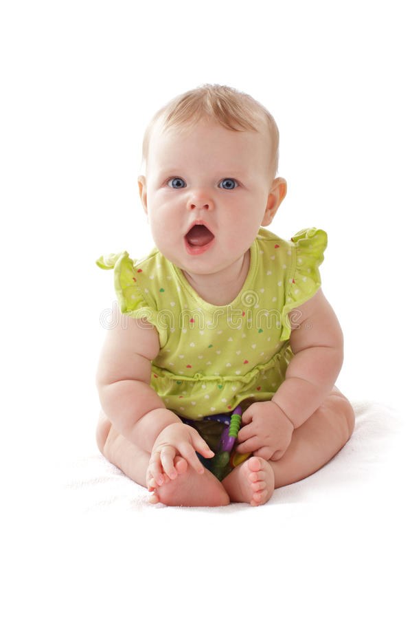 Adorable blue eyed baby sits and vocalizes. Pretty 6 month old baby girl with big blue eyes and ruffled dress sits and vocalizes. She holds a rattle. Pastels stock images