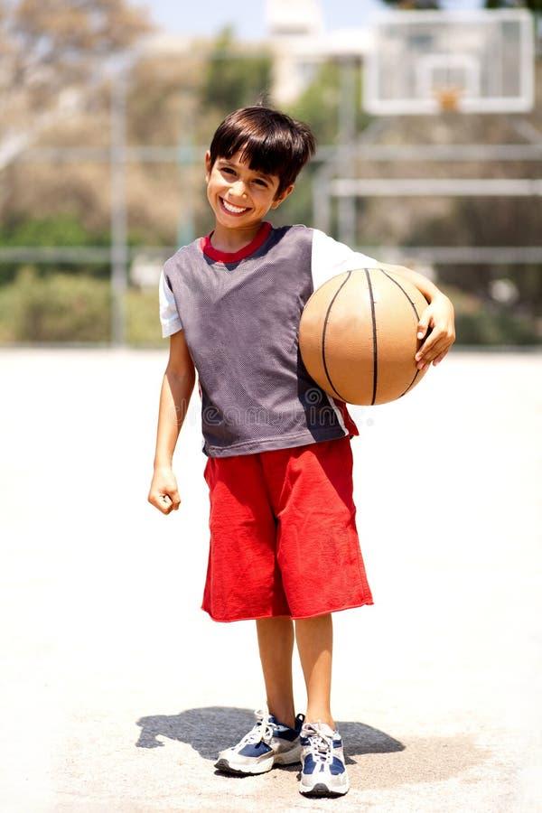 Adorable boy with basketball stock photography