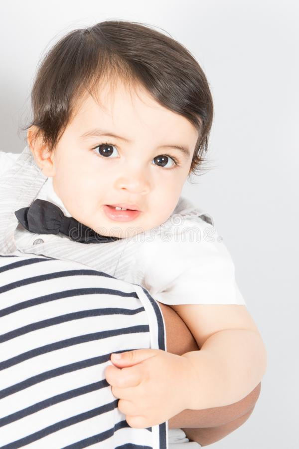 Adorable boy child in parent arms stock photography