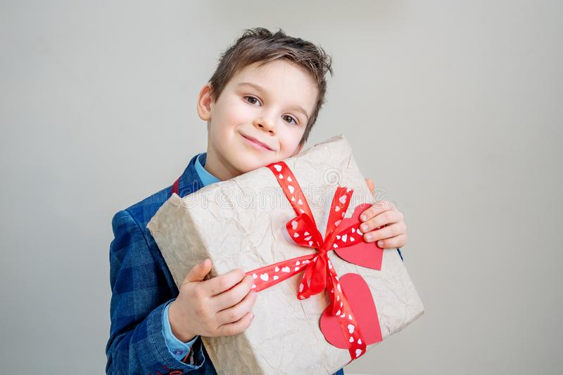 Adorable boy with a gift box on a light background royalty free stock photography