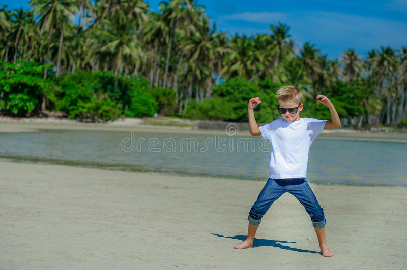 Adorable boy having fun on the tropical beach. White t-shirt, dark trousers and sunglasses. Barefoot on white sand. stock photos