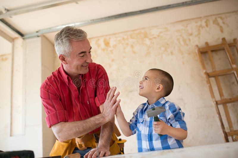 Adorable boy with his grandfather in teamwork stock photo