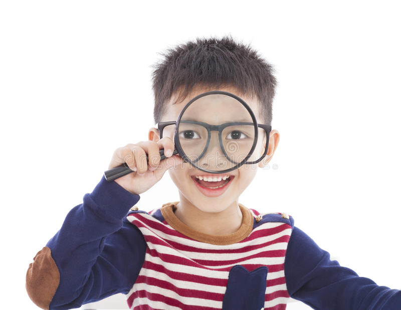 Adorable boy holding a magnifier and watching through royalty free stock images