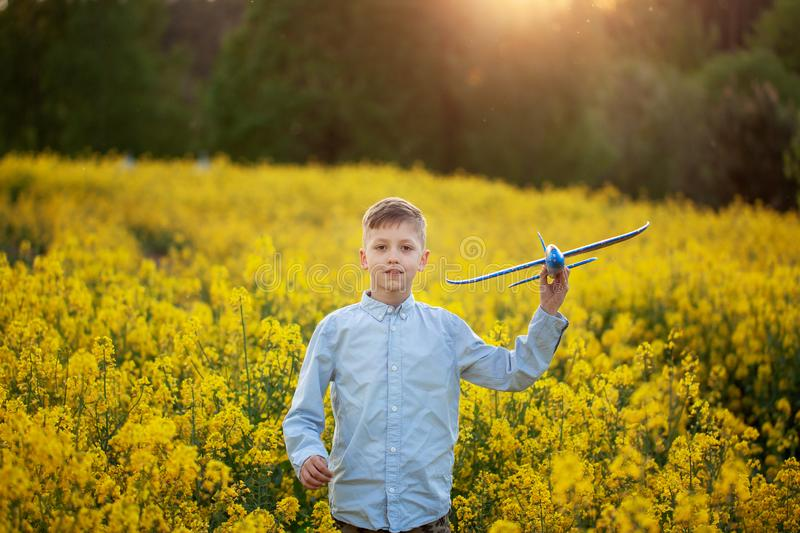 Adorable Boy holds toy plane in his hand on sunset in summer day stock image