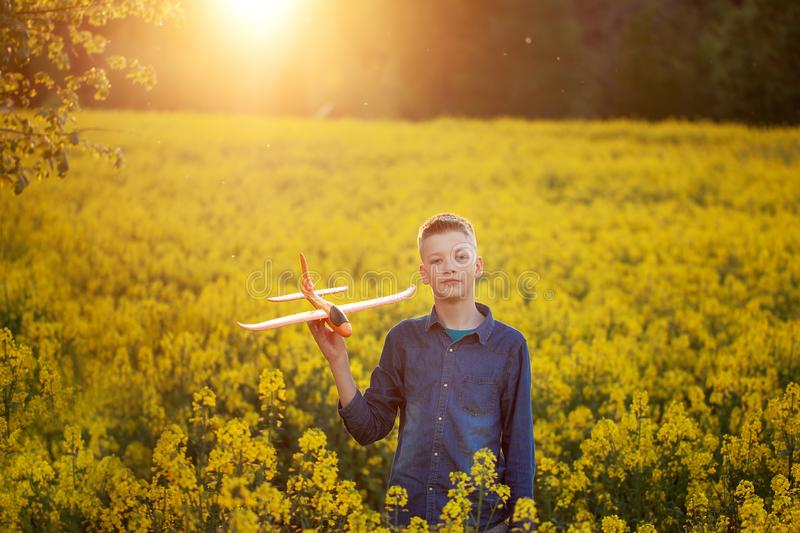 Adorable Boy holds toy plane in his hand on sunset in summer day stock photo