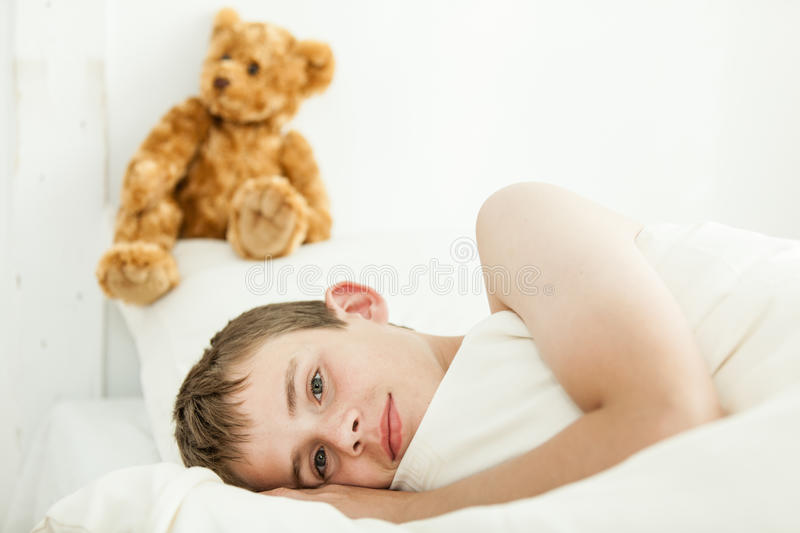 Adorable boy laying down near plush bear. Single adorable boy laying in bed with eyes open and covered by white sheets and blanket beside plush bear above his stock photo