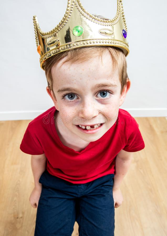 Adorable boy with missing tooth and crown, high angle portrait. Portrait of an adorable 7-year old boy with a missing tooth and a golden crown posing for child`s royalty free stock image