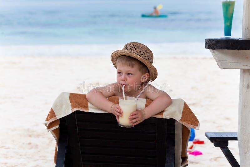 Adorable boy sipping milkshake stock photo