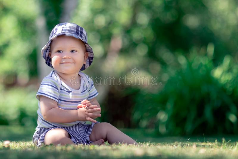 Adorable boy sitting on the grass and applaud. Cute baby sitting on the grass in the garden and applaud royalty free stock images