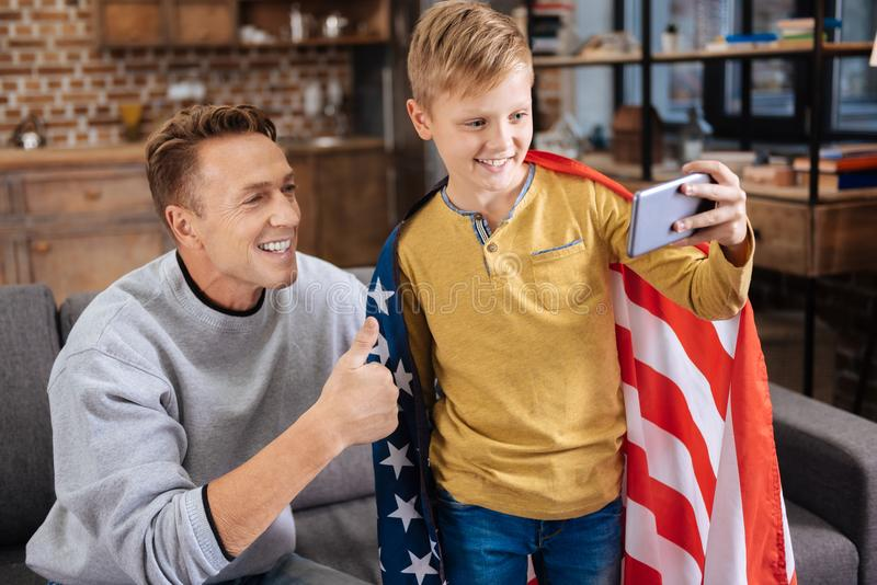 Adorable boy wrapped in US flag taking selfie with father. Patriotic family. Charming pre-teen boy wearing a US flag on his shoulders and taking a selfie with stock photos