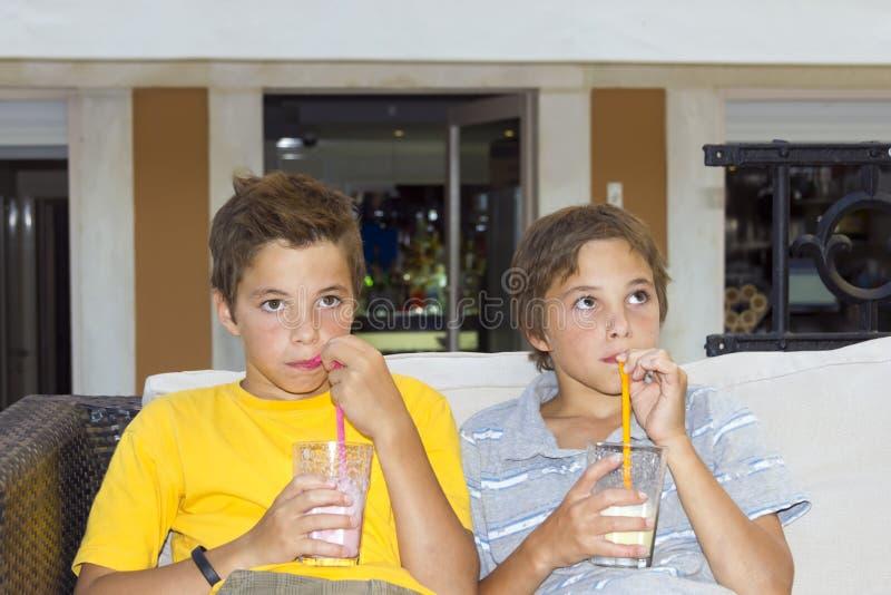 Adorable boys with glasses of milkshake royalty free stock photos