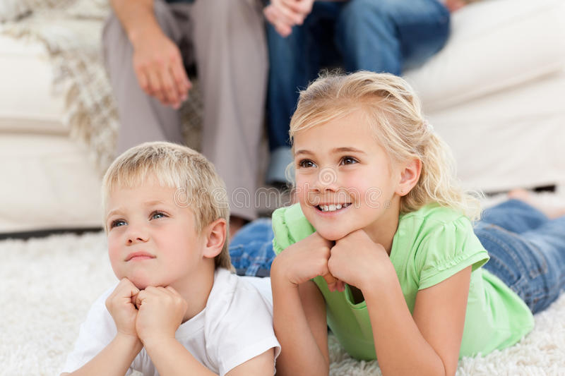 Adorable brother and sister watching tv royalty free stock photo