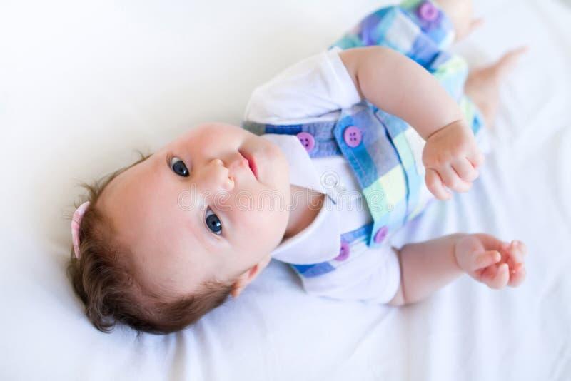 Adorable brunette baby girl in purple overalls stock image