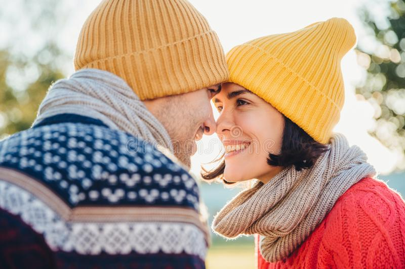 Adorable brunette female and her boyfriend stand closely to each other, look at eyes, smile happily as feel love and support. Good stock image
