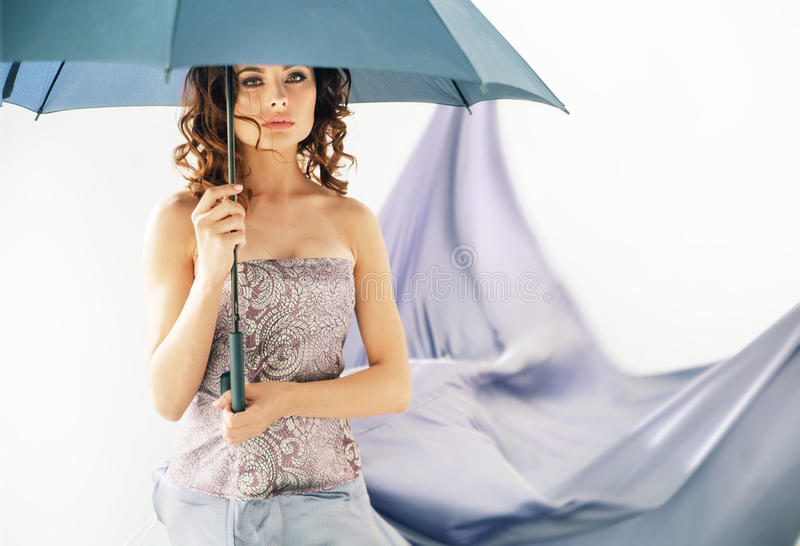 Adorable brunette woman holding an umbrella royalty free stock image