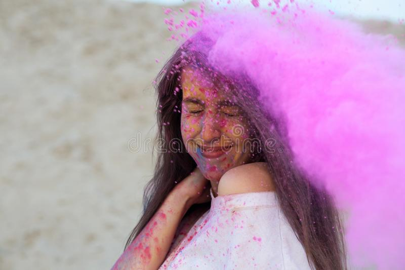 Adorable brunette model with long hair having fun with pink dry paint Holi at the desert. Adorable brunette woman with long hair having fun with pink dry paint stock images